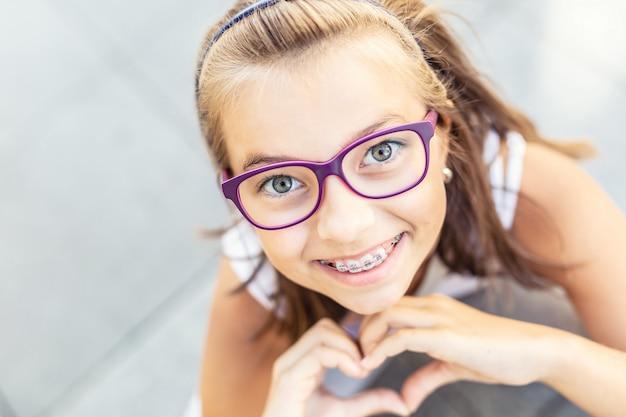 Jovem pré-adolescente de óculos usando aparelho sorri para a câmera, mostrando a forma do coração com as mãos.