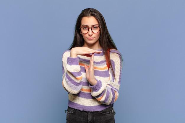 Jovem pré-mulher parecendo séria, severa, irritada e descontente, fazendo sinal de tempo limite. conceito de estudante