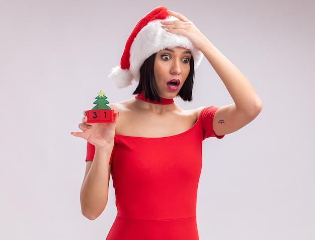 Jovem preocupada com chapéu de papai noel segurando um brinquedo da árvore de natal e olhando para baixo, mantendo a mão na cabeça isolada no fundo branco
