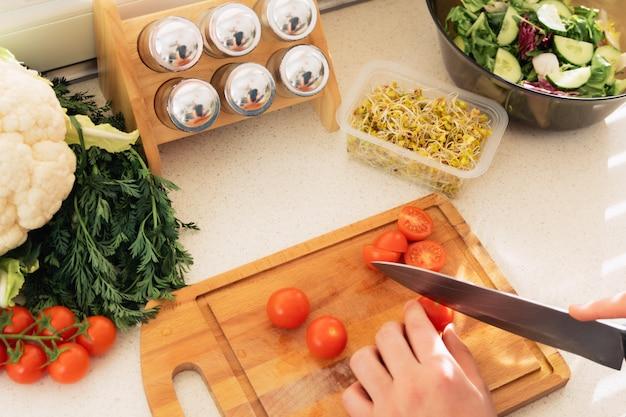 Jovem prepara uma salada muito saudável de vegetais orgânicos frescos e ervas