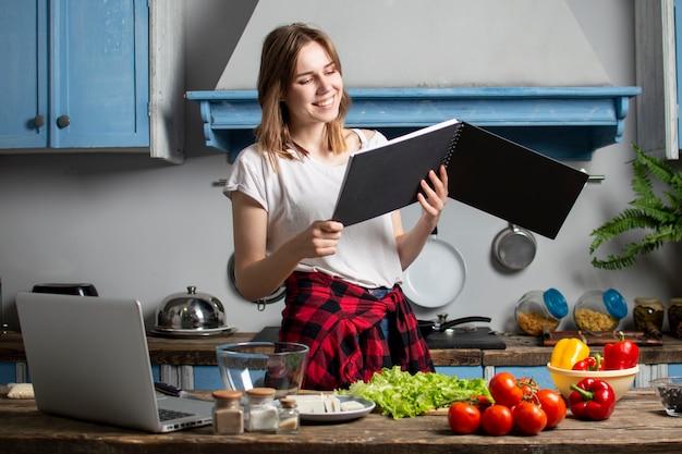 Jovem prepara uma salada vegetariana na cozinha e olha para um livro de receitas, ela aprende a cozinhar e lê