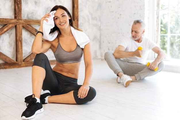 Jovem preparadora física positiva mantendo um sorriso no rosto e enxugando a testa enquanto coloca os braços sobre os joelhos