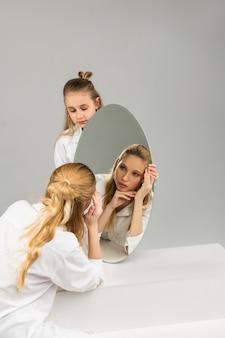 Jovem prestativa carregando cuidadosamente o espelho redondo enquanto sua irmã atenta se verifica nele