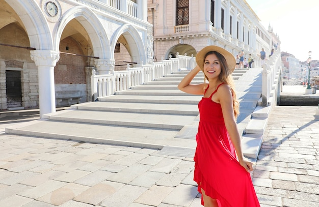 Jovem princesa animada em veneza pronta para subir as escadas para visitar a incrível cidade da itália