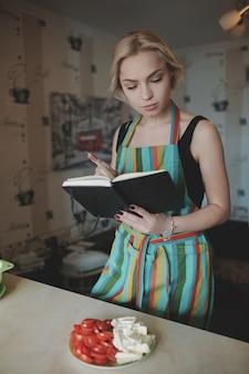 Jovem procurando em um livro de receitas