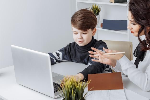 Jovem professor com criança fazendo lição de casa em um computador. ajuda do tutor.