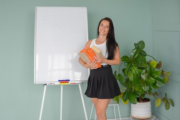 Jovem professor dá uma aula perto do quadro-negro com livros