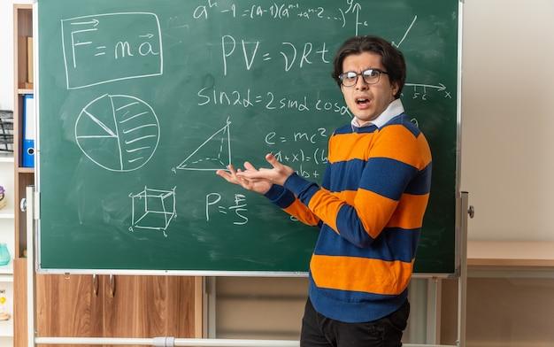 Jovem professor de geometria sem noção usando óculos em pé em vista de perfil na frente do quadro-negro na sala de aula olhando para frente apontando com as mãos para o quadro-negro