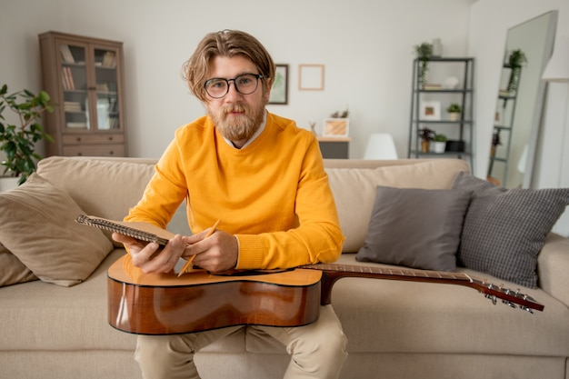 Jovem professor de música de sucesso em trajes casuais olhando para você enquanto está sentado no sofá e fazendo anotações no bloco de notas durante a aula online