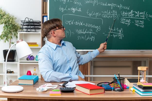 Jovem professor de óculos, explicando a lição, parecendo confiante, sentado na mesa da escola com livros e anotações na frente do quadro-negro na sala de aula