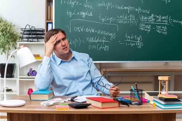 Jovem professor de óculos, parecendo cansado e sobrecarregado, tocando a cabeça sentado na mesa da escola com livros e anotações na frente do quadro-negro na sala de aula