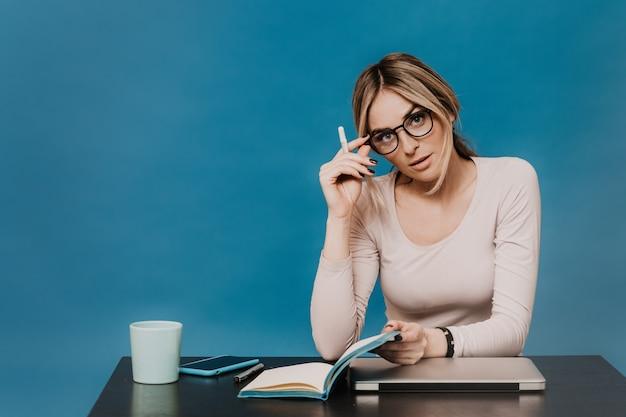 Jovem professor de óculos, sentado em uma mesa, verificando o trabalho de seus alunos trabalhando remotamente