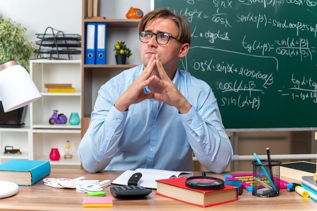 Jovem professor de óculos sentado na mesa da escola com livros e notas segurando as palmas das mãos juntas olhando para o lado com uma expressão pensativa no rosto pensando na frente do quadro-negro na sala de aula