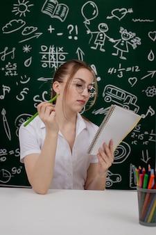 Jovem professor está sentado perto de quadro-negro em sala de aula