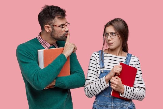 Jovem professor ou tutor segura livro vermelho velho, mostra sinal de silêncio, pede ao trainee para não espalhar boatos