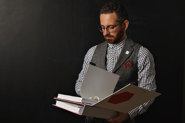 Jovem professor sério e descolado de camisa xadrez e colete de tweed em pé diante de uma lousa em branco e lendo uma pasta grossa de vermelho e branco