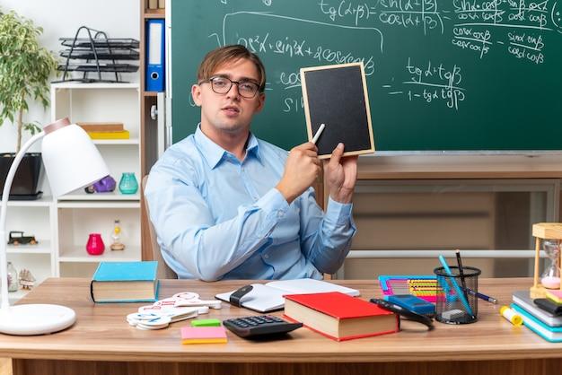 Jovem professor usando óculos com uma pequena lousa e um pedaço de giz explicando a lição, parecendo confiante, sentado na mesa da escola com livros e anotações na frente da lousa na sala de aula