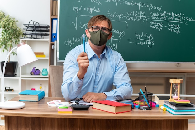 Jovem professor usando óculos e máscara protetora facial mostrando um lápis com cara séria, sentado na mesa da escola com livros e anotações na frente do quadro-negro na sala de aula