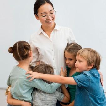 Jovem professora abraçando seus alunos