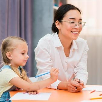 Jovem professora ajudando a menina na sala de aula