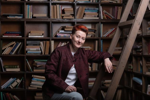 Jovem professora ao lado da escada com o fundo da estante de livros