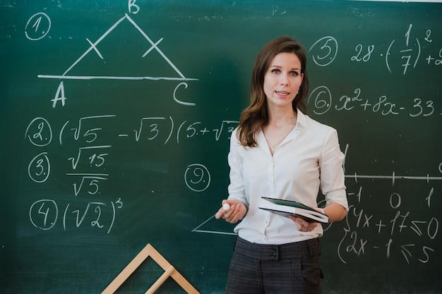 Jovem professora atraente de matemática, interagindo com seus jovens alunos da escola primária, pedindo uma resposta para uma jovem