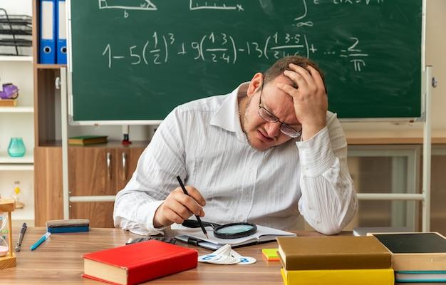 Jovem professora carrancuda usando óculos, sentada na mesa com o material escolar na sala de aula, segurando um lápis, mantendo a mão na cabeça, olhando para baixo