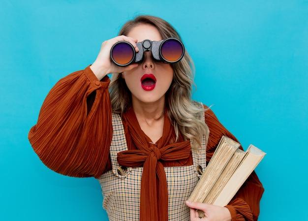 Jovem professora com livros e binóculos em azul