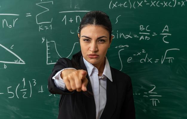 Jovem professora confiante em pé na frente do quadro-negro aponta para a frente na sala de aula