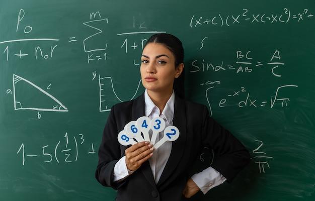 Jovem professora confiante em pé na frente do quadro-negro, segurando leques numéricos, colocando a mão a bordo na sala de aula