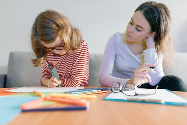 Jovem professora dando aula particular para criança