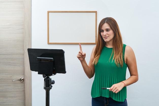 Jovem professora dando aulas online em casa por videochamada. conceito de novas tecnologias, estudo e aulas online.