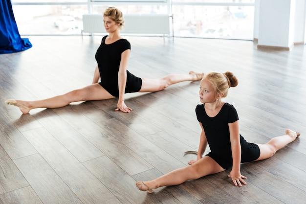 Jovem professora de balé e sua pequena aluna na aula de balé
