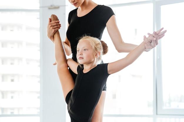 Jovem professora de balé e sua pequena aluna no estúdio de balé