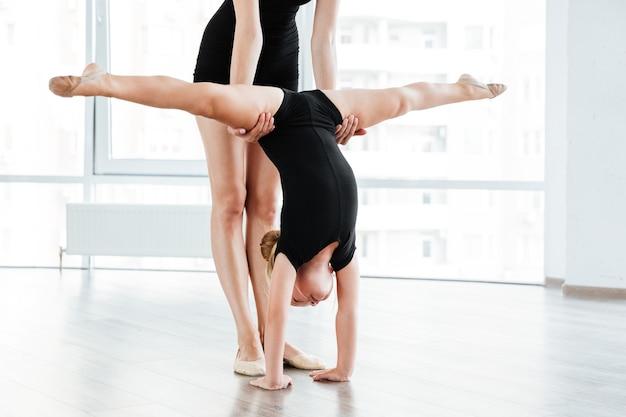 Jovem professora de balé e sua pequena aluna no estúdio de dança
