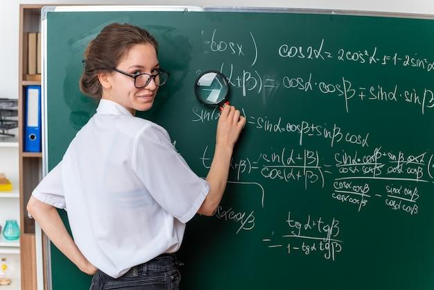 Jovem professora de matemática satisfeita usando óculos, parada atrás de uma visão na frente do quadro-negro
