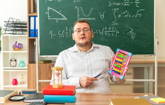 Jovem professora impressionada usando óculos, sentada na mesa com o material escolar na sala de aula, segurando o ábaco apontando para ele com um ponteiro apontando para a frente
