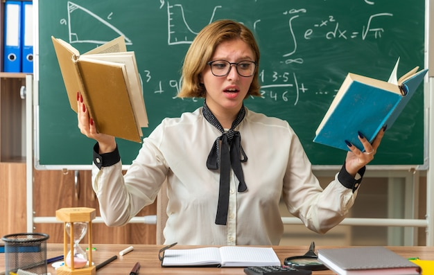 Jovem professora insatisfeita de óculos, sentada à mesa com ferramentas escolares, lendo um livro na sala de aula