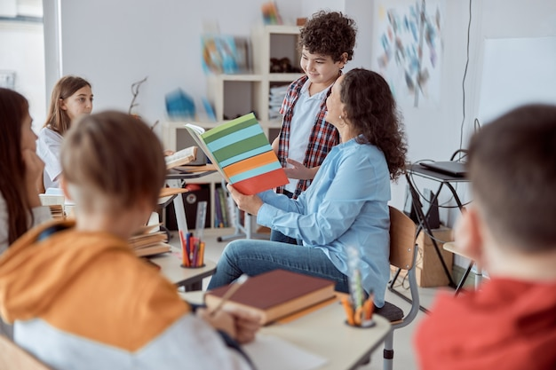 Jovem professora lendo com seu aluno na frente de toda a classe. crianças do ensino fundamental sentadas em mesas e lendo livros em sala de aula.