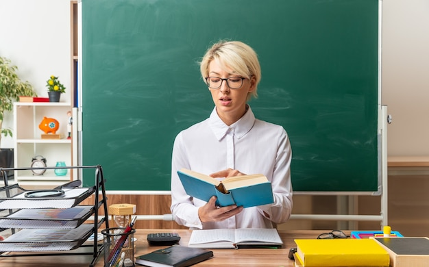 Jovem professora loira impressionada de óculos, sentada na mesa com as ferramentas da escola na sala de aula, segurando e apontando o dedo no livro lendo-o