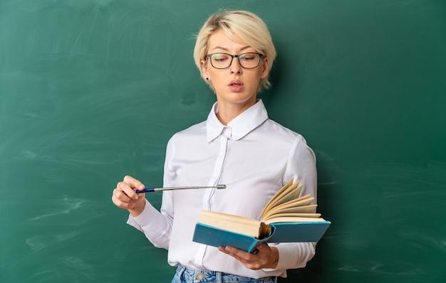 Jovem professora loira impressionada usando óculos na sala de aula em frente ao quadro-negro segurando a leitura e apontando com o ponteiro para o livro com espaço de cópia