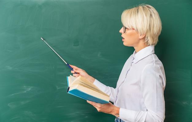 Jovem professora loira impressionada usando óculos na sala de aula em pé em vista de perfil na frente do quadro-negro segurando o livro olhando e apontando com o ponteiro no quadro-negro
