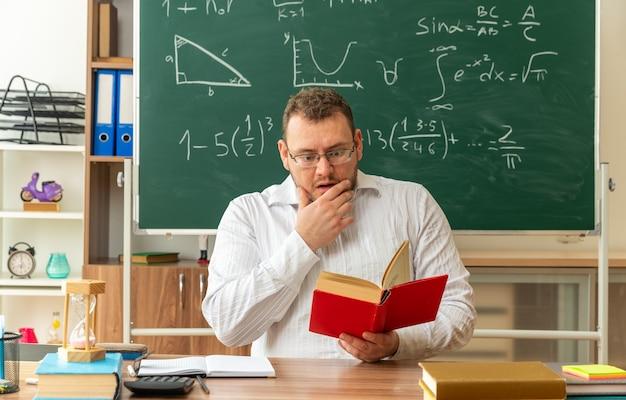 Jovem professora loira preocupada com óculos, sentada na mesa com as ferramentas da escola na sala de aula, lendo um livro e segurando o queixo