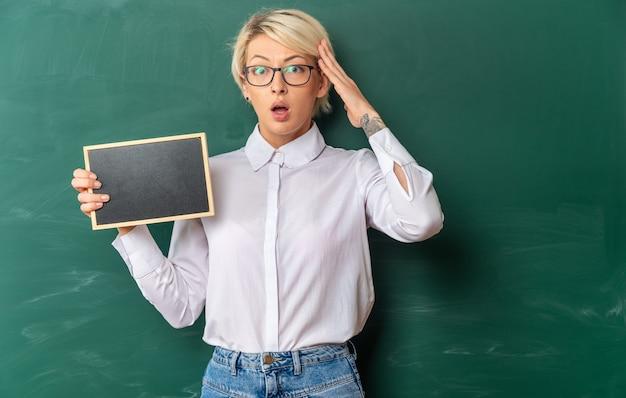 Jovem professora loira preocupada usando óculos em uma sala de aula em frente ao quadro-negro, mostrando uma minilousa com as mãos na cabeça, olhando para frente com espaço de cópia