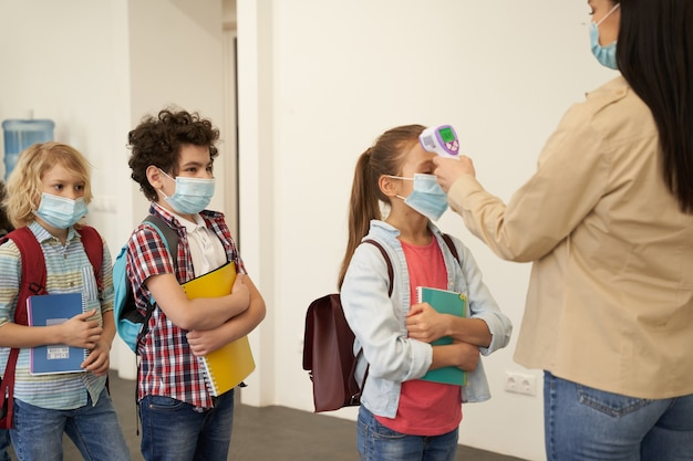Jovem professora na fila de espera usando máscara protetora para medir a temperatura de crianças com