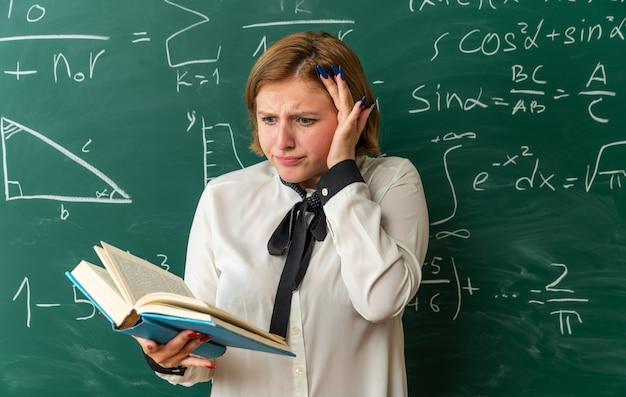 Jovem professora preocupada em pé na frente da lousa lendo um livro na sala de aula