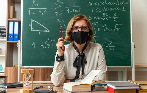 Jovem professora preocupada, usando óculos e máscara médica, está sentada à mesa com ferramentas escolares segurando um lápis na sala de aula