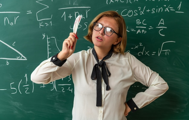 Jovem professora rígida usando óculos, parada na frente do quadro-negro, segurando leques e colocando a mão no quadril na sala de aula