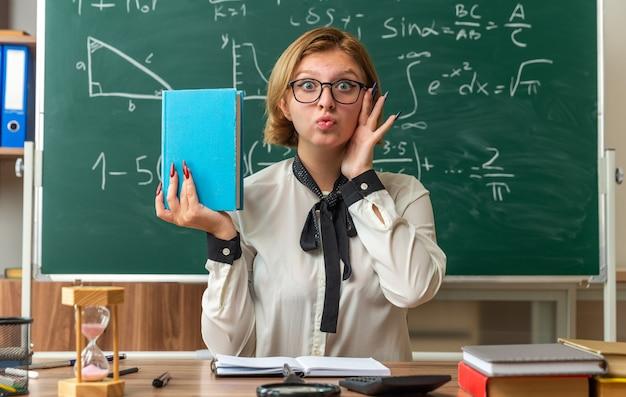 Jovem professora satisfeita de óculos, sentada à mesa com ferramentas escolares, segurando um livro na sala de aula