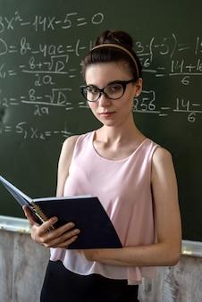 Jovem professora séria explica fórmulas matemáticas na universidade ao lado do quadro-negro